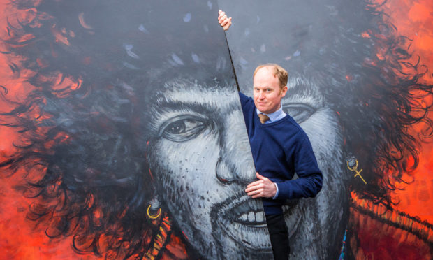 Auctioneer Nick Burns with the large-scale Hendrix portrait