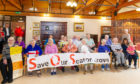 Some of the residents and supporters with the banner made to highlight the potential closure of the facility.