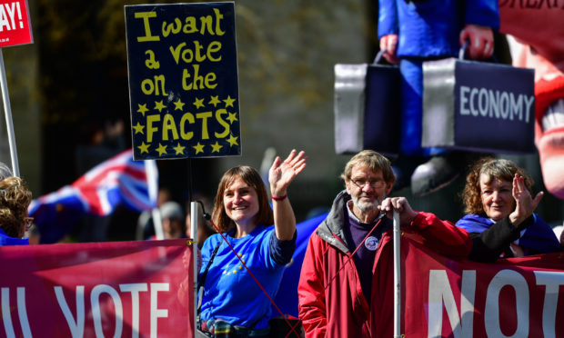 "Members of the public wave to oncoming traffic holding a sign saying ""I want a vote on the facts"" outside the Houses of Parliament, Westminster."