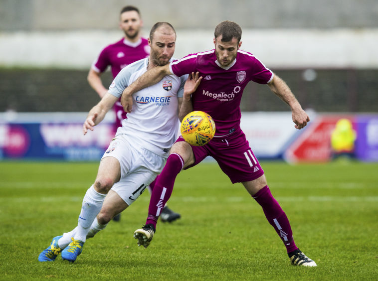Montrose's Sean Dillon (L) in action with Arbroath's Danny Denholm.