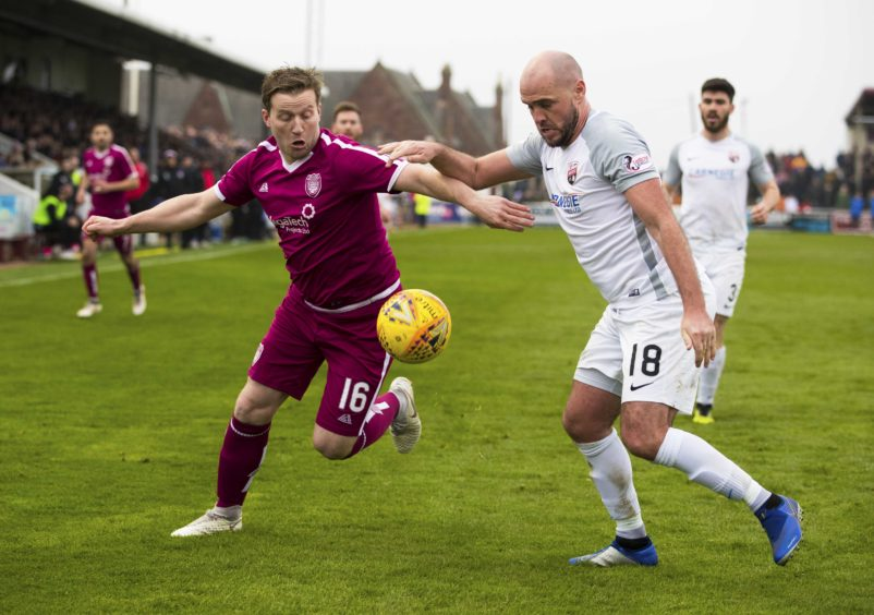 Arbroath's Steven Doris (L) in action with Montrose's Iain Campbell.