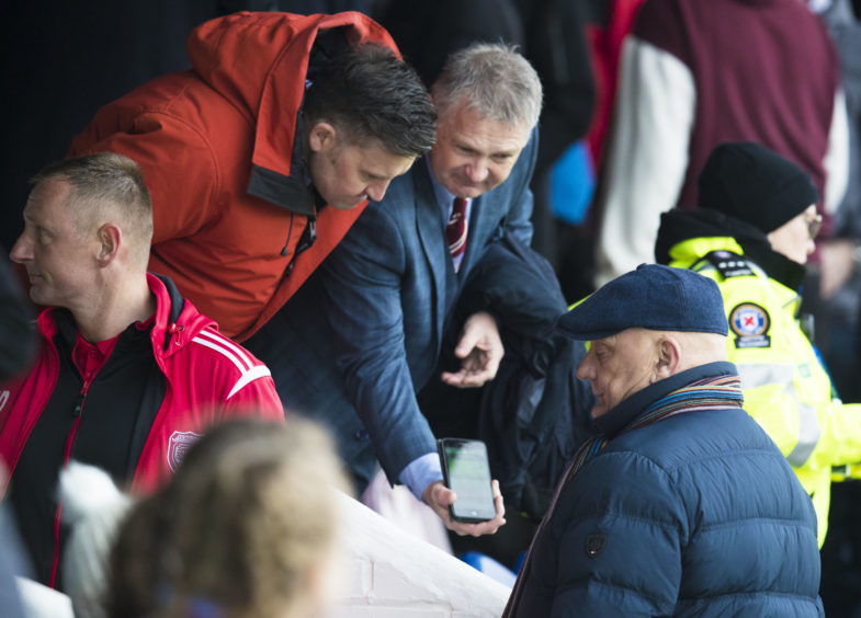 Arbroath manager Dick Campbell (R) is shown the score from the Stenhousemuir v Raith Rovers match.