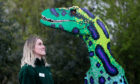 Laura McDowell from Marwell Zoo looks up at a Velociraptor.
