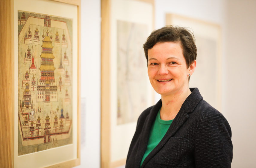 World mapping expert Dr Diana Lange from Humbolt University in Berlin pictured within Wise Collection exhibition at The McManus.