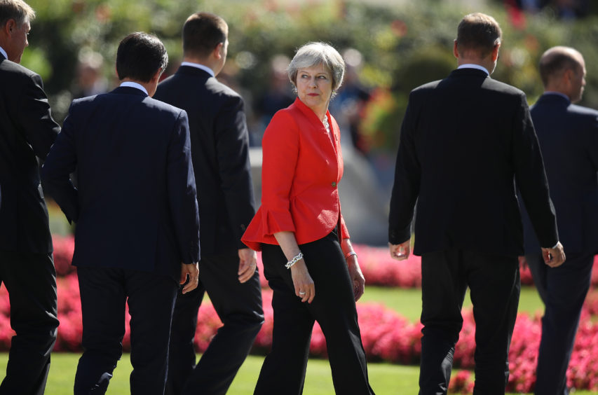 British Prime Minister Theresa May looks back as she and other leaders depart following the family photo on the second day of an informal summit of leaders of the European Union on September 20, 2018 in Salzburg, Austria. High on the agenda of the two-day summit is migration policy.