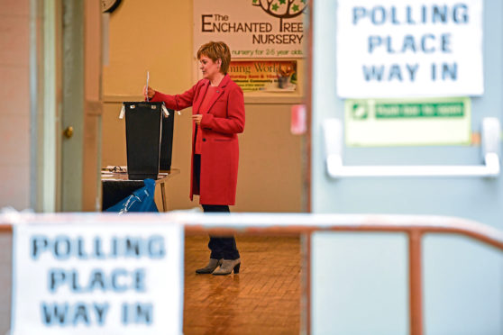 First Minister of Scotland and leader of the Scottish National Party, Nicola Sturgeon casts her vote in the European parliament election with her husband Peter Murrell at Broomhouse Community Hall.