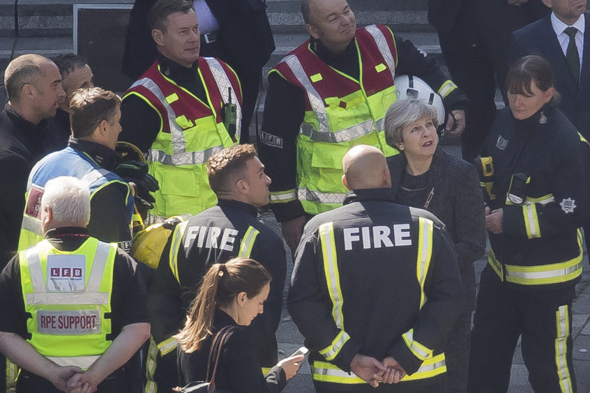 Prime Minister Theresa May speaks to members of the fire service as she visits Grenfell Tower, on June 15, 2017 in London, England. At least twelve people have been confirmed dead and dozens missing, after the 24 storey residential Grenfell Tower block in Latimer Road was engulfed in flames in the early hours of June 14. The number of fatalities are expected to rise.