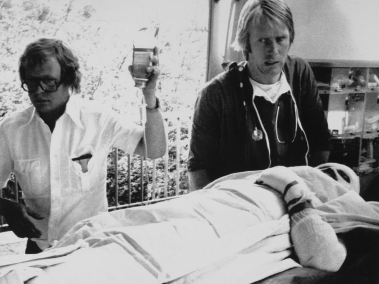 Austrian racing driver Niki Lauda is carried into hospital at Ludwigshaven after suffering serious burns when his Ferrari caught fire during the German Grand Prix at Nurburgring, August 1976.