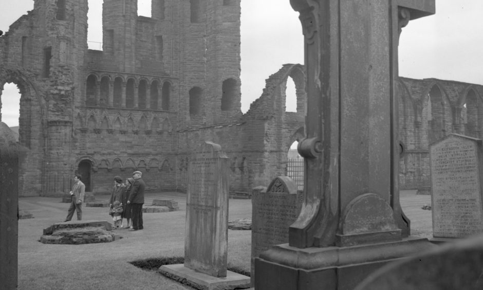 Visitors to Arbroath Abbey stand not far from the high altar, with the magnificent ruins of the South Transept and the round O of Arbroath in the background. At one period the Round O served as a beacon for mariners. 1963.