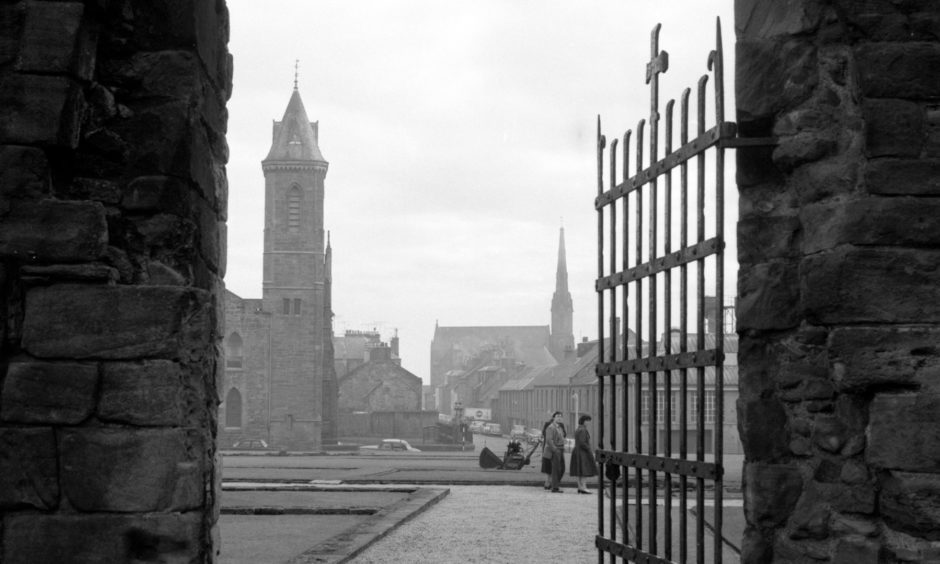 Looking through one of the Abbey Church doors to the churches and the town of Arbroath across the former cloisters of the Abbey. 1963.