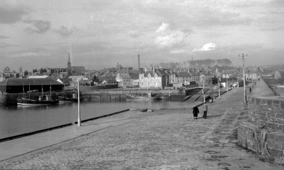 View of Arbroath Harbour from the harbour wall, overlooking the fishing boats to the town beyond. The ruins of Arbroath Abbey can be seen on the skyline on the left hand side. 1962.