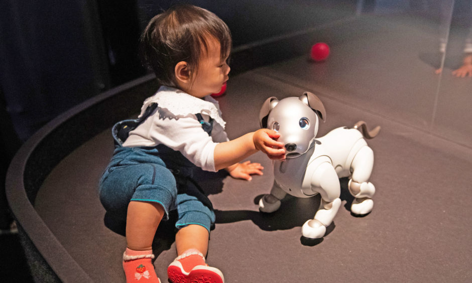 Charlotte Xie, aged one, interacts with Sony's robot puppy 'Aibo' at a press preview for AI: More Than Human exhibition. The major new exhibition explores the relationship between humans and artificial intelligence.