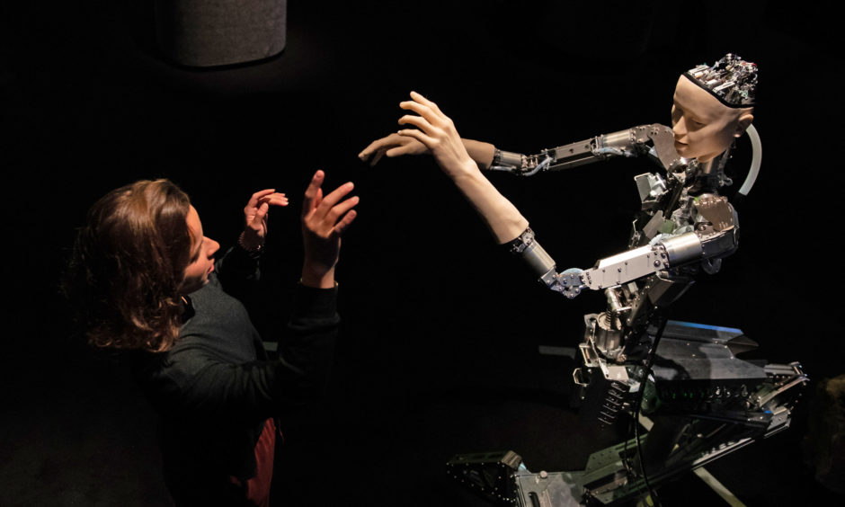 A women interacts with 'Alter', a machine body with a human like face and hands who learns through interplaying with the surrounding world.