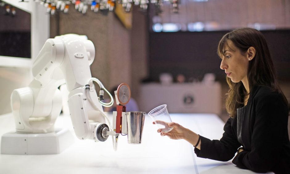 A women interacts with a robotic bartender called 'Makr Shakr'.