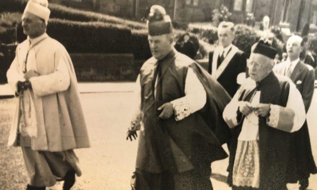 Clergy walk through the town, circa 1960s