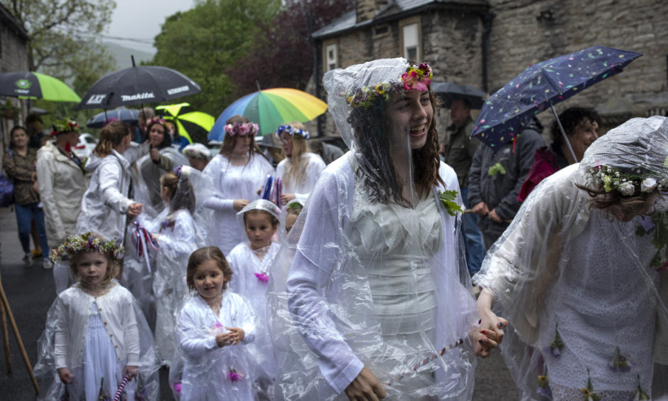 May pole dancers laugh as the rain pours down during 'Castleton Garland Day'
