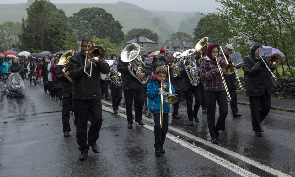A brass band leads a procession through the village.