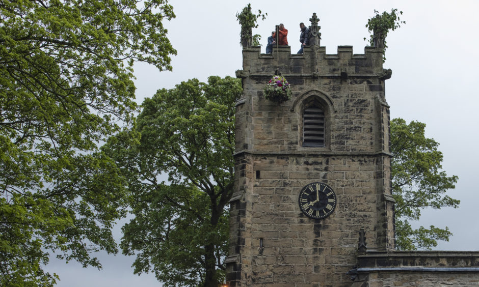 The Garland is hoisted from 'The King' and up to the Church roof during 'Castleton Garland Day'.