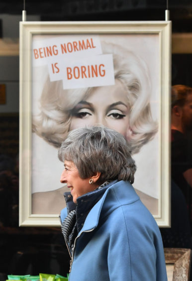 File photo dated 04/03/19 of Prime Minister Theresa May passing a display in a shop window while walking through Salisbury on the first anniversary of the Skripal poisoning. The Prime Minister is expected to announce details later today of her timetable for leaving Downing Street.