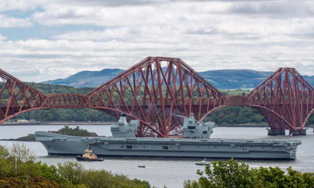 The HMS Queen Elizabeth sails under the Forth Bridges as she heads south from Rosyth after completing some routine maintenance work in the dockyard.