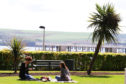 Two girls have a picnic in the sun amongst the palm trees on Perth Road.