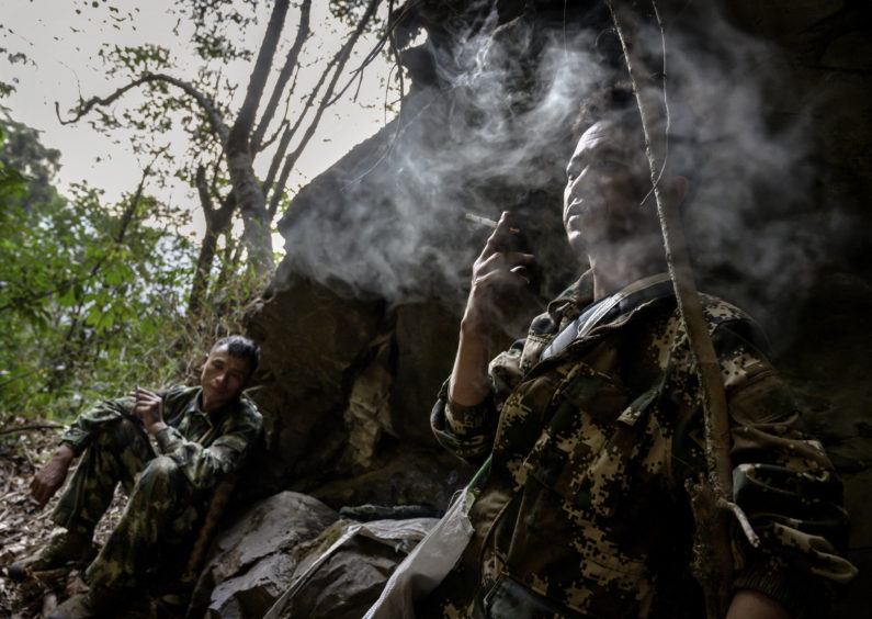 Chinese ethnic Lisu honey hunter Mi Qiaoyun, left, and helper Dongwu smoke as thye rest after gathering wild cliff honey from hives in a gorge on May 10, 2019 near Mangshi, in Dehong prefecture, Yunnan province China.