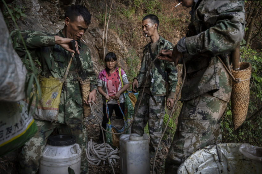 Chinese ethnic Lisu honey hunters Dong Haifa,center, and Mi Qiaoyun,left, and Ma Yongde stand with containers of honey after gathering wild cliff honey from hives in a gorge on May 10, 2019 near Mangshi, in Dehong prefecture, Yunnan province China.