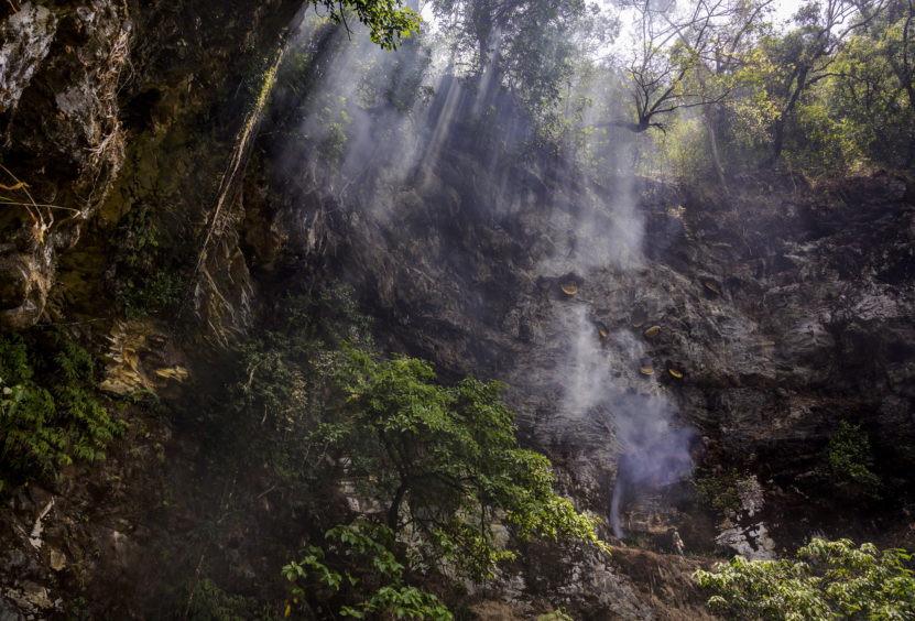 Chinese ethnic Lisu honey hunter sets a fire for smoke while he and others were gathering wild cliff honey in a gorge on May 10, 2019 near Mangshi, in Dehong prefecture, Yunnan province China.