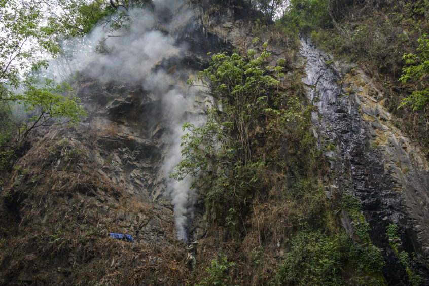 Chinese ethnic Lisu honey hunters light a fire to make smoke before gathering wild cliff honey from hives in a gorge on May 30, 2019 near Mangshi, in Dehong prefecture, Yunnan province China.