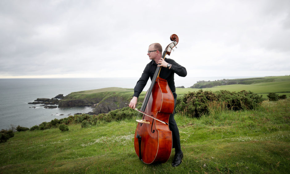 Musician Scott Matheson from the #iPlay4Peace crowdsourced global orchestra plays his double bass on the Black Hill near the Stonehaven War Memorial in Aberdeenshire, an unfinished Greek temple representing the unfinished lives taken by war, ahead of the 100th anniversary of the signing of the Treaty of Versailles.
