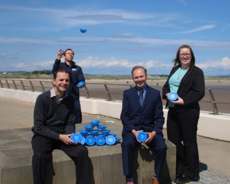 Stephen Gethins MP, Scot Fraser and Mike Will of Scottish Water and ,Vicky Walker, of Fife Council's environmental health team handed out gunk pots in St Andrews to celebrate the success of the fat-busting scheme.