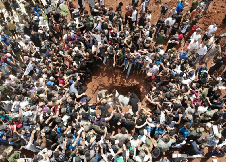 A picture taken with a drone on June 9, 2019 shows Syrians attending the burial of late rebel fighter Abdel-Basset al-Sarout in al-Dana in Syria's jihadist-controlled Idlib region, near the border with Turkey. - The Syrian goalkeeper turned rebel fighter who starred in an award-winning documentary died on June 8 of wounds sustained fighting regime forces in northwestern Syria, his faction said. Sarout, 27, was among dozens of fighters killed since June 6 in clashes with regime forces on the edges of the Idlib region.