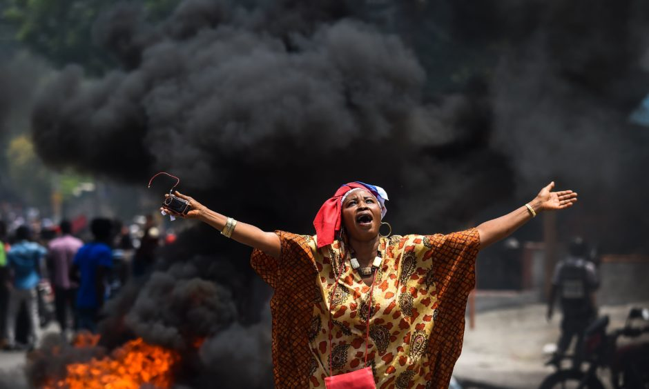 A demonstrator holds up her arms and chants slogans during a protest against the ruling government in Port-au-Prince on June 9, 2019. - A man was killed on the sidelines of the demonstration that gathered several thousand demonstrators on June 9 in Port-au-Prince demanding the resignation of President Jovenel Moise over allegations of embezzlement.