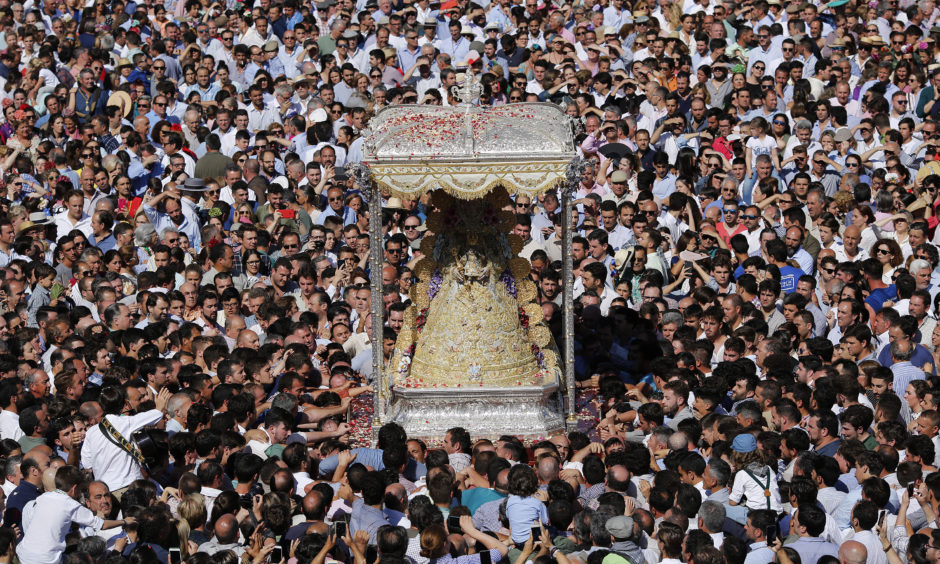Pilgrims crowd around the Virgin of El Rocio during a procession around the shrine of El Rocio on June 10, 2019 in Almonte, Spain. Every spring thousands of devotees converge at a shrine to pay homage to the Virgin  del Rocio during an annual religious pilgrimage.
