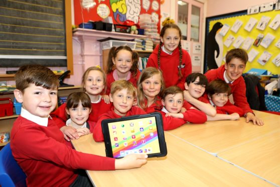 """Nine-year-old Angus Gordon with the an IPad and the other members of the Liff Leaders""""of Liff Primary School,"""