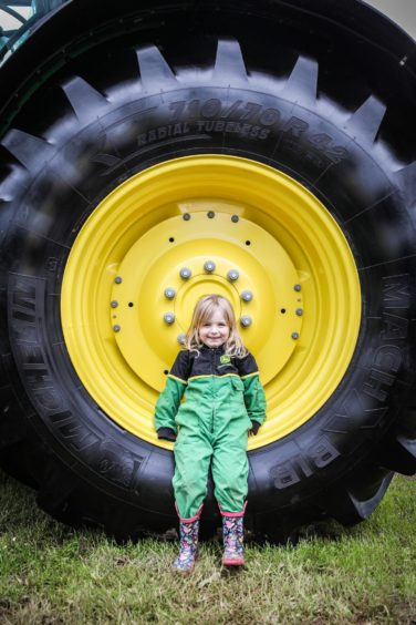 Holly Hughes being dwarfed by a John Deere tractor tyre.
