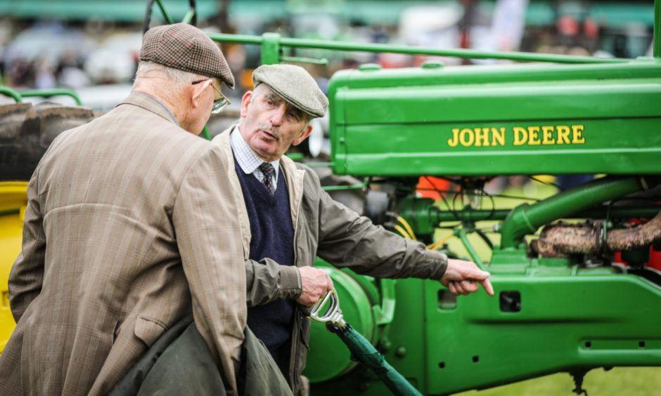 People inspecting the vintage tractors.