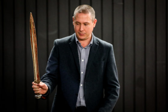 Warren Bailie with a reconstruction of a bronze age sword found at the site