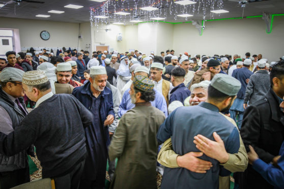 People embrace after prayers and celebrations at Dundee Islamic Society mosque to celebrate Eid.