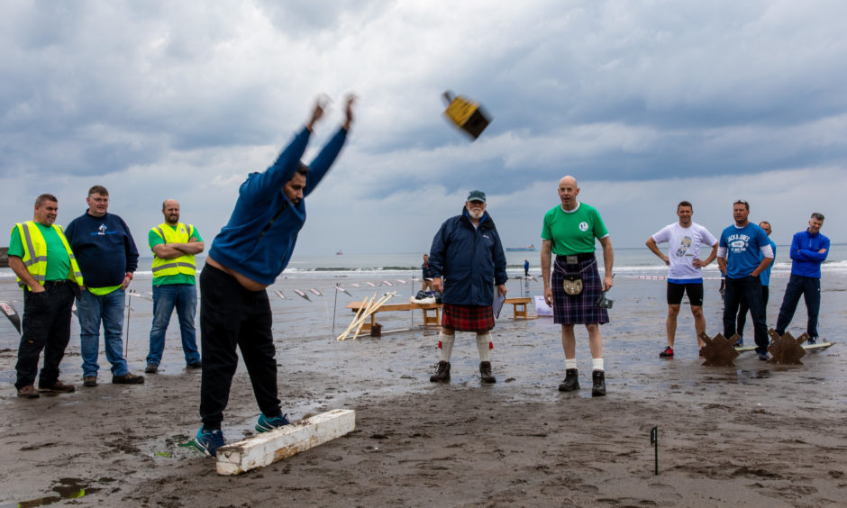 Members of the public compete in the block throw as part of the Beach Highland Games. Steve Brown / DCT Media