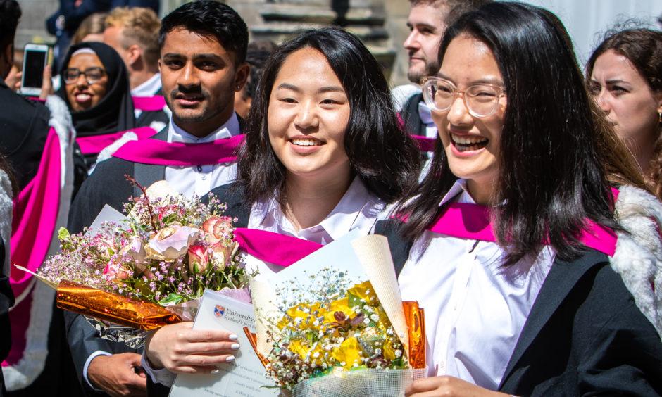 Graduates hold celebratory flowers.