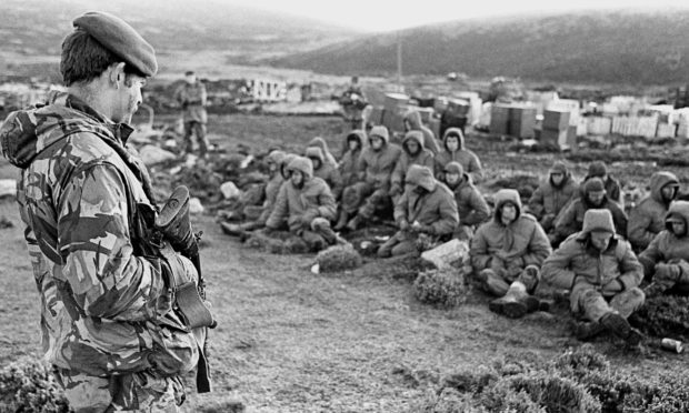 Argentinian soldiers captured at Goose Green are guarded by a British Royal Marine as they await transit out of the area.
