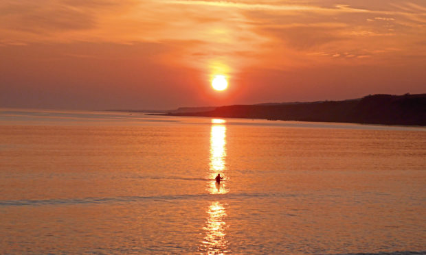 Anna Palmer is captured during a stunning sunrise swim in St Andrews.