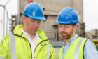 Caltech Lifts Managing Director Andrew Renwick (right) looks over the plans for the industrial lift installation with his brother, technical director Fraser Renwick.