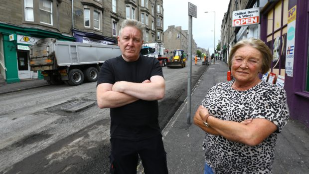 Abe McIntosh of Household Clearnces and Sandra Small of The Tanning Lounge beside the roadworks in Albert Street, Dundee.