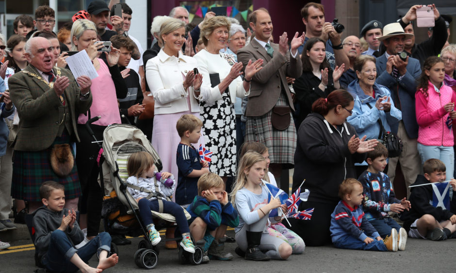 The Earl and Countess of Forfar applaud a highland dancing performance.