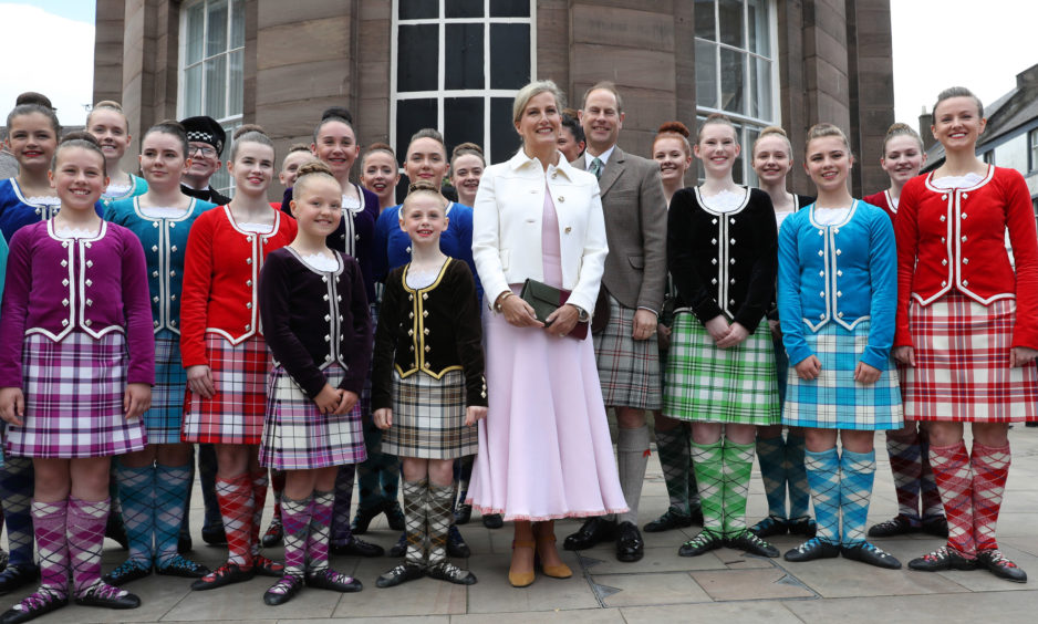 The Earl and Countess of Forfar pose for a photograph with dancers after watching a highland dancing performance.