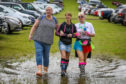 Gail Whyte (49), Leanne Williamson (39) and Elaine Lawrence (48) from Dundee, don't let a puddle stop them heading into Rewind.