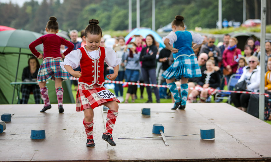 Highland Dancers take to the stage in front of the two judges.