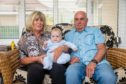 Anne Anderson (64), Baby Maximus Redfern-Anderson (5mth) and Stuart Anderson (64) from Tullibody at home after their stay